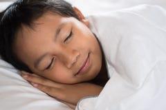 Muchacho que duerme con la cara de la sonrisa en la hoja y la almohada blancas de cama Foto de archivo libre de regalías