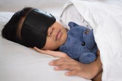Muchacho que duerme en cama con la almohada blanca y las hojas del oso de peluche que llevan la máscara del sueño imagenes de archivo