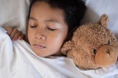 Muchacho que duerme en cama con la almohada y las hojas blancas del oso de peluche Foto de archivo