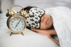 Muchacho que duerme en el piilow y las hojas blancos de la cama con la máscara del sueño del clork de la alarma que lleva imagenes de archivo