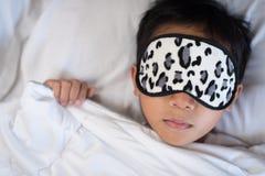 Muchacho que duerme en la almohada y las hojas blancas de la cama con la máscara del sueño Imagenes de archivo