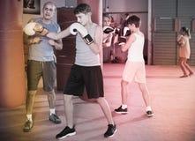 Muchacho que ejercita en el boxeo en el gimnasio con el coche Imagen de archivo