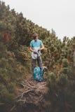 Muchacho que embala su ropa para hacer excursionismo en rastro Fotos de archivo