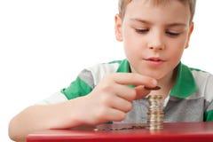 Muchacho que empila encima de las monedas aisladas en blanco fotos de archivo libres de regalías