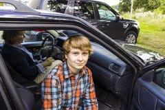 muchacho que entra en el coche Imagen de archivo libre de regalías