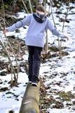 Muchacho que equilibra encendido inicio de sesión el invierno Imagenes de archivo