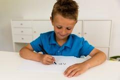 Muchacho que escribe el alfabeto de ABC Imagen de archivo
