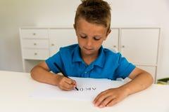 Muchacho que escribe el alfabeto de ABC Imagenes de archivo