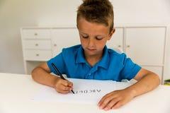 Muchacho que escribe el alfabeto de ABC Imágenes de archivo libres de regalías
