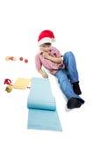 Muchacho que escribe una letra muy larga a Papá Noel en el fondo blanco Fotos de archivo libres de regalías