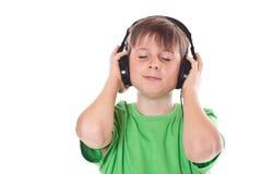 Muchacho que escucha la música con los auriculares Imagenes de archivo