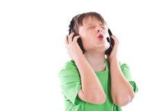 Muchacho que escucha la música con los auriculares Fotografía de archivo