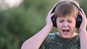 Muchacho que escucha la música con los auriculares Imágenes de archivo libres de regalías