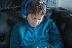 Muchacho que escucha la música con los auriculares azules Imagen de archivo libre de regalías