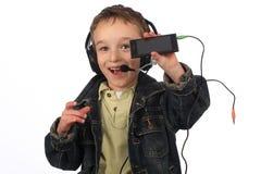 Muchacho que escucha la música en el fondo blanco Imagen de archivo