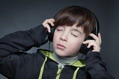 Muchacho que escucha la música en los auriculares Fotografía de archivo