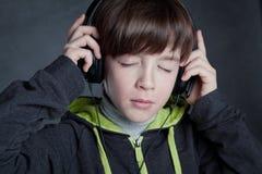 Muchacho que escucha la música en los auriculares Imagenes de archivo