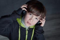 Muchacho que escucha la música en los auriculares Imágenes de archivo libres de regalías