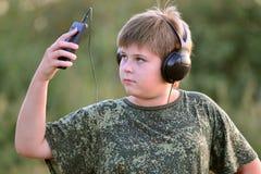 Muchacho que escucha la música en los auriculares con smartphone Imagen de archivo