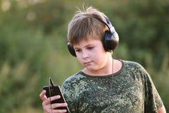 Muchacho que escucha la música en los auriculares con smartphone Imagenes de archivo