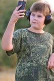 Muchacho que escucha la música en los auriculares con smartphone Foto de archivo