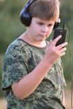 Muchacho que escucha la música en los auriculares con smartphone Fotografía de archivo