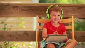 Muchacho que escucha la música en los auriculares verdes almacen de video
