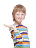 Muchacho que estira hacia fuera su brazo con la palma para arriba, mirada, sonriendo Foto de archivo