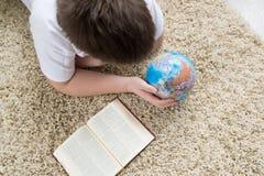 Muchacho que estudia el globo y el libro de lectura Fotos de archivo