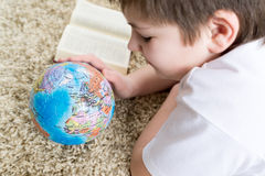 Muchacho que estudia el globo y el libro de lectura Foto de archivo libre de regalías