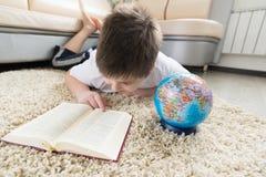 Muchacho que estudia el globo y el libro de lectura Imágenes de archivo libres de regalías