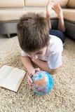 Muchacho que estudia el globo y el libro de lectura Fotos de archivo libres de regalías