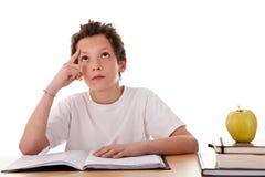 Muchacho que estudia y que piensa, junto con uno en manzana Fotografía de archivo libre de regalías