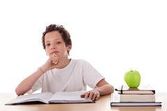 Muchacho que estudia y que piensa, junto con uno en manzana Foto de archivo libre de regalías
