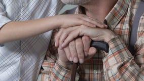 Muchacho que frota ligeramente a los abuelos mano, afecto de la familia, ayuda en el problema, relaciones almacen de metraje de vídeo