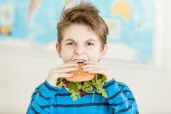 Muchacho que frunce el ceño como él muerde en una hamburguesa del veggie Imágenes de archivo libres de regalías