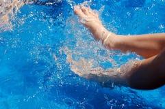 Muchacho que golpea con el pie en piscina Fotos de archivo libres de regalías