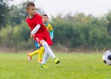 Muchacho que golpea el balón de fútbol con el pie Imágenes de archivo libres de regalías