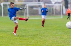 Muchacho que golpea el balón de fútbol con el pie Imagenes de archivo
