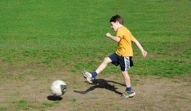 Muchacho que golpea el balón de fútbol con el pie Fotos de archivo libres de regalías