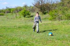 Muchacho que golpea el balón de fútbol con el pie colorido en campo Fotos de archivo libres de regalías