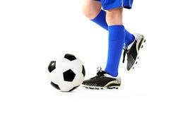 Muchacho que golpea el balón de fútbol con el pie Fotografía de archivo libre de regalías