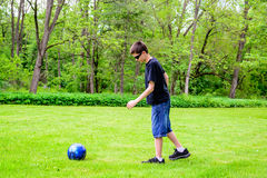 Muchacho que golpea el balón de fútbol con el pie Fotos de archivo