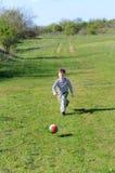 Muchacho que golpea el balón de fútbol con el pie colorido en campo Imagen de archivo libre de regalías
