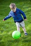 Muchacho que golpea la bola con el pie imágenes de archivo libres de regalías