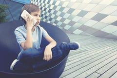 Muchacho que habla en el teléfono móvil en la ciudad Fotografía de archivo
