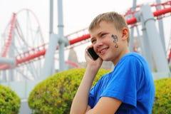 Muchacho que habla en un móvil en un parque de atracciones Fotos de archivo