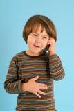 Muchacho que habla en un teléfono móvil Foto de archivo libre de regalías