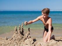 Muchacho que hace el castillo de la arena en la playa Fotos de archivo