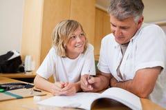 Muchacho que hace la preparación con su padre fotografía de archivo libre de regalías